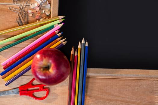 Close-up of chalkboard with colored pencil and apple #415480
