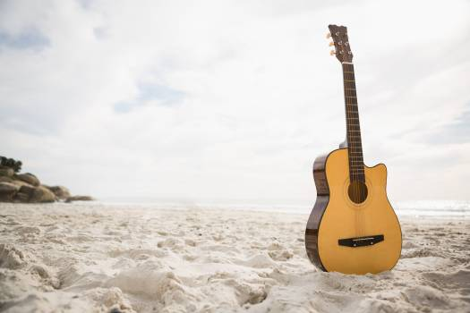 Acoustic guitar standing in the sand Free Photo