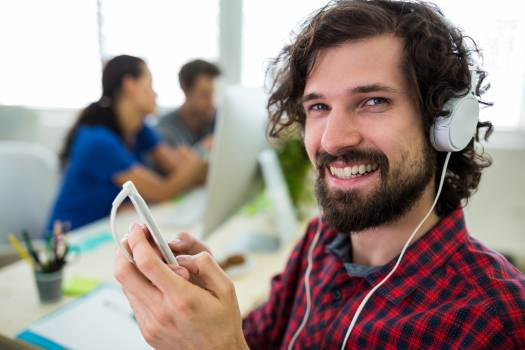 Male graphic designer listening music from mobile phone #415691