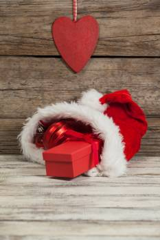 Red Christmas bauble and gift kept in santa hat #415854
