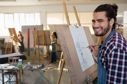 Portrait of smiling man painting on paper #415896