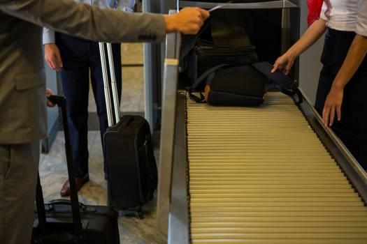 Female staff checking passengers luggage on conveyor belt #415922
