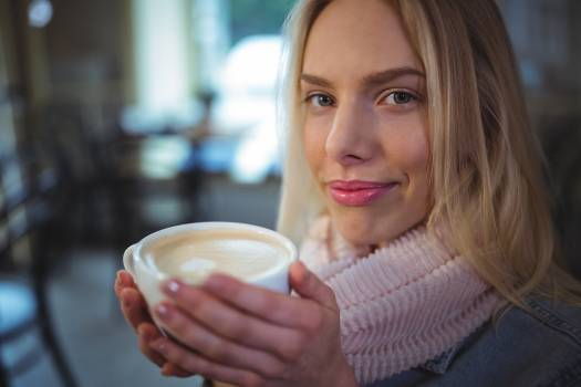Beautiful woman having a cup of coffee in café #415939