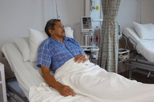 Mature male patient relaxing on bed in medical ward at hospital #415944