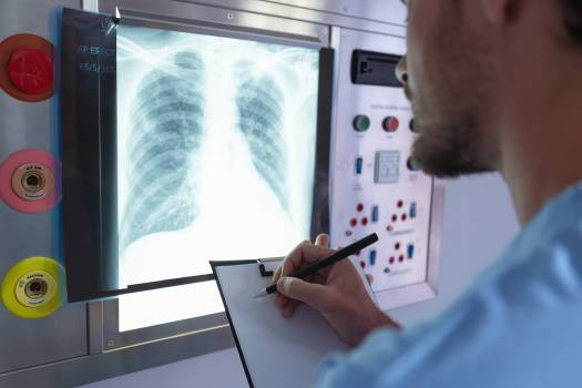 Male surgeon writing on clipboard while examining x-ray on x-ray light box in operation room #415946