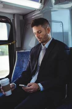 Businessman holding a disposable coffee cup and using mobile phone Free Photo