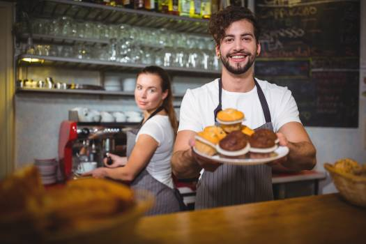 Portrait of waiter holding a plate of cup cake at counter Free Photo