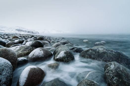 Misty White and Dark Green Water over Grey Stones Free Photo