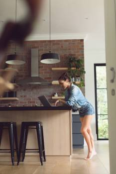 Woman using laptop on worktop in kitchen at comfortable home  #416172