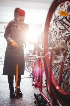 Mechanic filling air into bicycle tire with air pump #416180