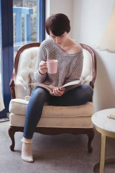 Woman having coffee while reading a magazine at home #416205