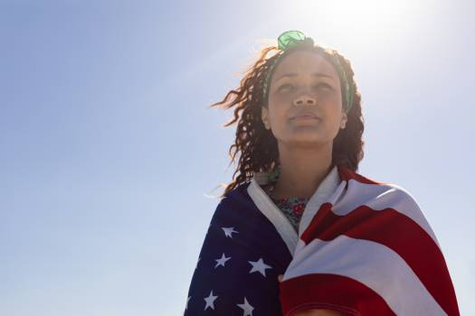 Beautiful young woman wrapped in american flag on beach in the sunshine #416315