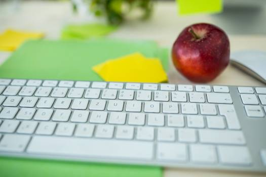 Close-up of a keyboard with apple on desk #416333