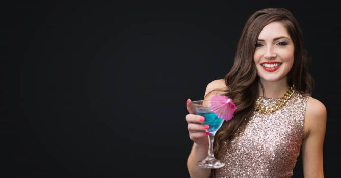 Woman with cocktail against dark grey background #416342