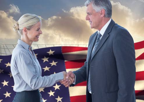 Business executives shaking hands against american flag in background #416370