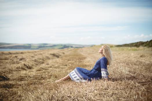 Blonde woman sitting in field #416377
