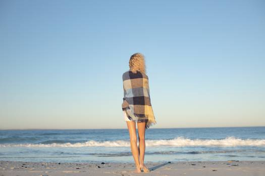 Woman wrapped in blanket standing on the beach #416444