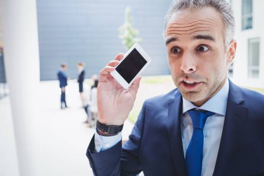 Businessman holding mobile phone and frowning Free Photo