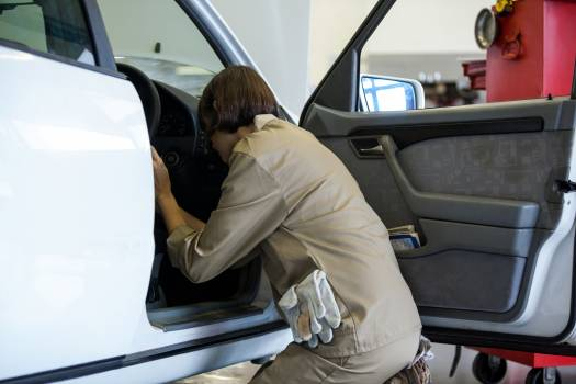 Female mechanic examining a car #416517