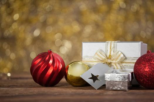 Wrapped gift box and baubles on wooden table #416594