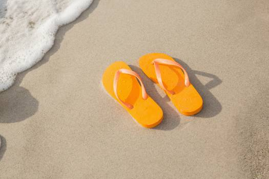 Orange flip flop in sand #416645