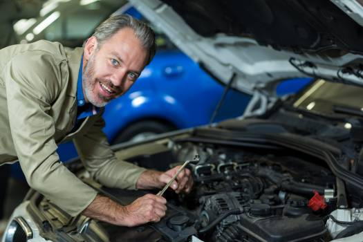 Mechanic smiling while servicing a car engine #416659