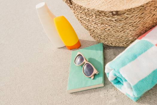 Close-up of bag and beach accessories on sand Free Photo