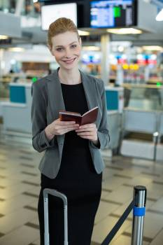 Smiling businesswoman with luggage checking her boarding pass Free Photo