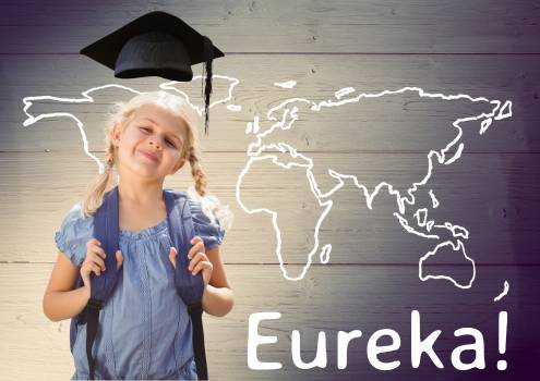 Text eureka and smiling schoolgirl standing against wooden background Free Photo