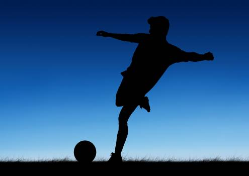 Soccer player kicking a ball against blue background #416716