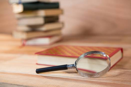 Magnifying glass with a book on a table #416885