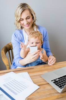 Mother and baby sitting at table and using mobile phone Free Photo