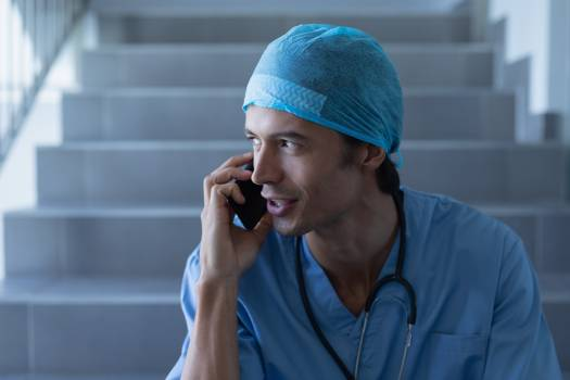 Male surgeon talking on mobile phone while sitting at stairs #416933