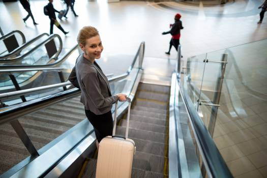 Businesswoman standing on escalator with luggage #417009