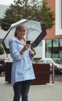 Beautiful woman holding umbrella while using mobile phone #417097
