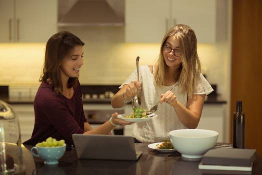 Happy friends using laptop while having breakfast in kitchen #417115