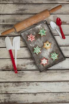 Spatula, spoon, rolling pin and tray with baked Christmas cookies #417182