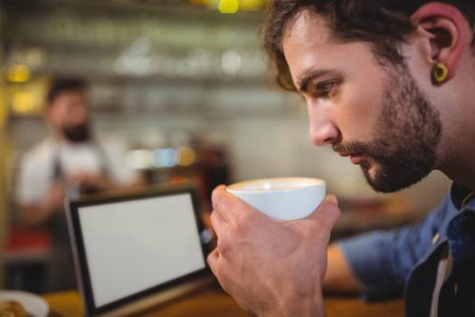 Man using digital tablet while having coffee in café #417208