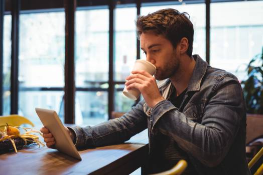 Man using digital tablet while having coffee #417217