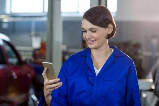 Female mechanic using mobile phone #417307
