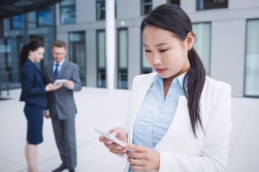 Businesswoman using mobile phone Free Photo