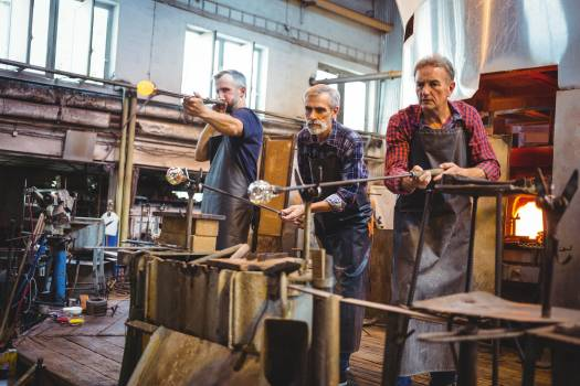 Team of glassblowers shaping a glass on the blowpipe #417397