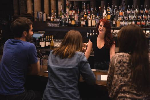 Bartender interacting with customers #417465