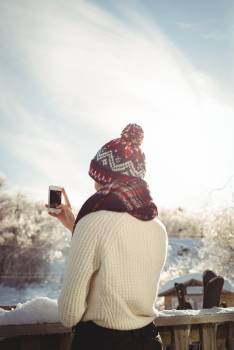Woman taking a photograph using mobile phone at ski resort #417523
