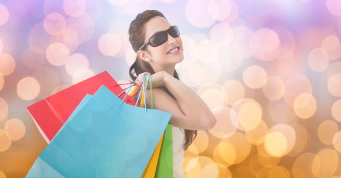Woman wearing sunglasses while carrying shopping bags over bokeh #417527