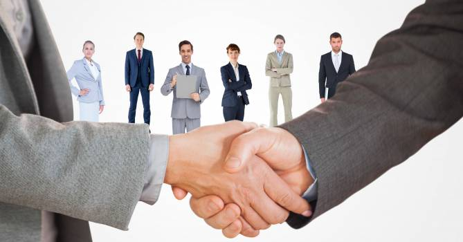 Cropped image of business people doing handshake with employees in background Free Photo