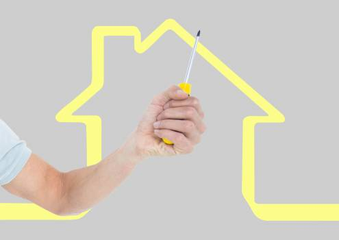 Hand with screwdriver with yellow house background #417549
