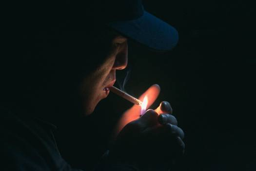 Man in Black Cap Lighting Cigarette during Nighttime Free Photo