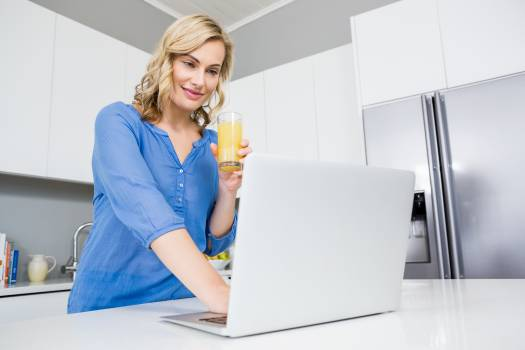 Beautiful woman holding a glass of juice using laptop in kitchen #417671