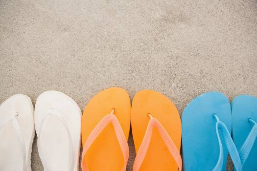 Multi-color flip flops arranged in a row in sand #417684